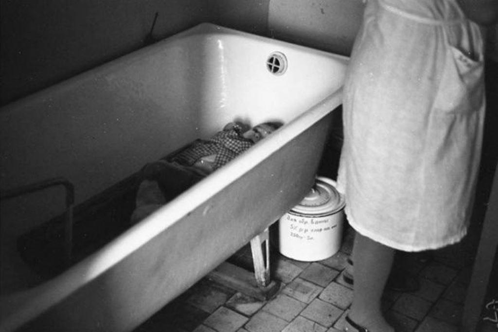 «Один в ванной», пока надевают сухие штаны на одного ребенка, другой дожидается своей очереди в ванной, Дом ребенка № 2. Новокузнецк, 29 мая 1981 года.
